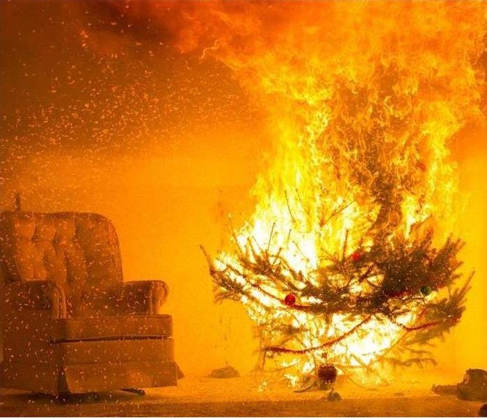 A Christmas tree positioned in front of curtains engulfed in orange and yellow fire flames.