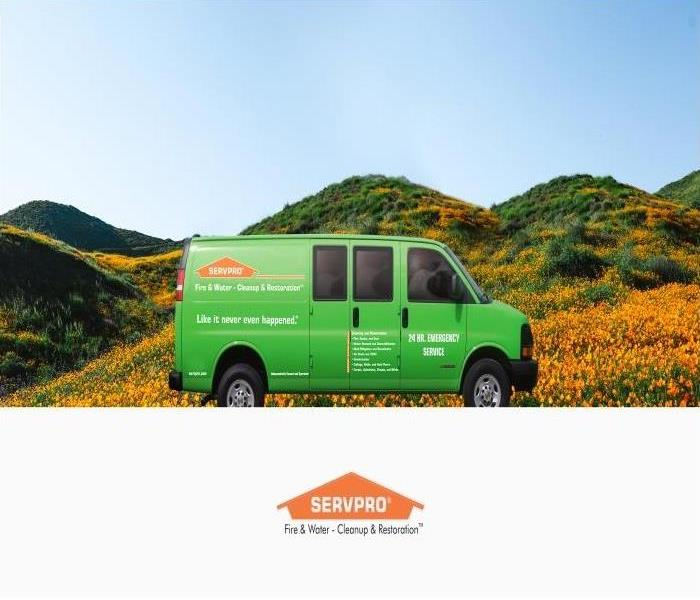 Green SERVPRO van in front of a hill of orange poppies, blue skies