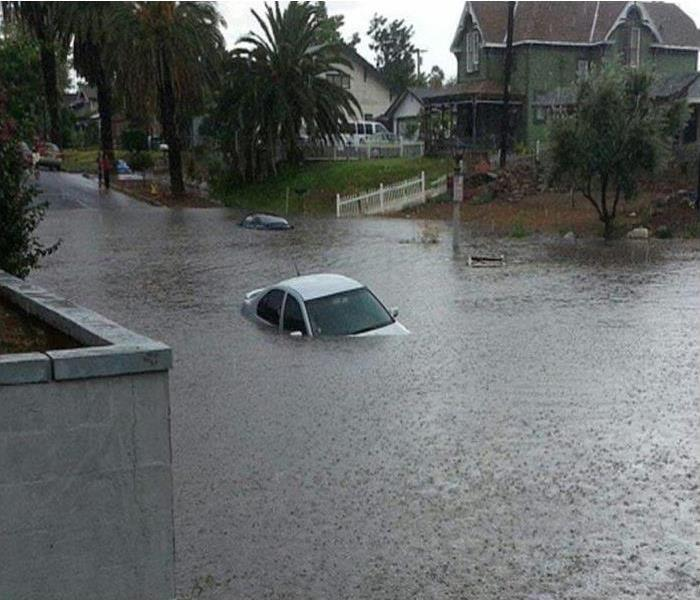 homes with street flooded with rain water and a car in the flood water